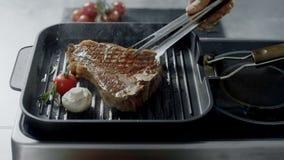 Cuoco unico che cucina bistecca alla pentola della piastra Mani dell'uomo del primo piano che girano bistecca con le tenaglie video d archivio