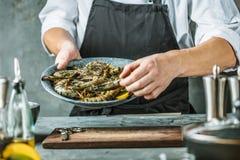 Cuoco unico che cucina con il gamberetto della tigre su fondo scuro immagine stock libera da diritti