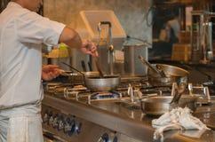 Cuoco unico che cucina con la pentola nella cucina Fotografia Stock Libera da Diritti