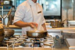 Cuoco unico che cucina con la pentola nella cucina Fotografie Stock