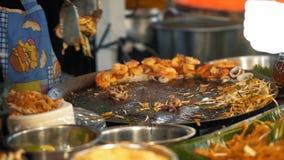 Cuoco unico che cucina cuscinetto tailandese con la tagliatella ed i frutti di mare sul wok al mercato dell'alimento di notte Ali video d archivio