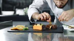 Cuoco unico che cucina dolce nel luogo di lavoro Mani maschii del primo piano che finiscono dessert archivi video