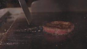 Cuoco unico che cucina e che preme dalla carne succosa per l'hamburger, alimento della spatola della via stock footage