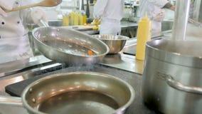 Cuoco unico che cucina le verdure in pentola nella cucina del ristorante o dell'hotel video d archivio
