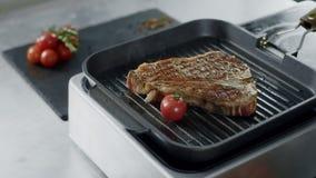 Cuoco unico che cucina lo steakn della griglia Mani del cuoco unico del primo piano che mettono le verdure a friggere forcella archivi video