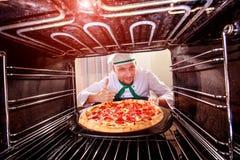 Cuoco unico che cucina pizza nel forno Fotografia Stock