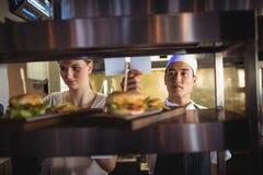 Cuoco unico che esamina una lista di ordine nella cucina commerciale Immagini Stock