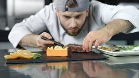 Cuoco unico che fa dolce nel luogo di lavoro Panettiere del primo piano che mette dessert al rallentatore stock footage