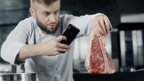 Cuoco unico che fa la foto della carne con il telefono cellulare Cuoco unico maschio che prende foto di bistecca stock footage