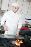 Cuoco unico che frigge la bistecca di manzo sulla griglia Fotografia Stock