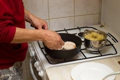 Cuoco unico che frigge le salsiccie fotografia stock