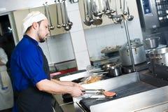 Cuoco unico che frigge un pesce sulla griglia Immagine Stock Libera da Diritti