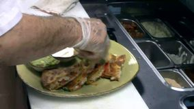 Cuoco unico che guarnisce un piatto dell'alimento di quesadilla archivi video