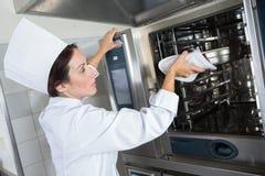 Cuoco unico che mette alimento in forno immagine stock libera da diritti