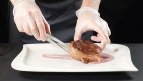 Cuoco unico che mette bistecca sul piatto Cucinando nel ristorante di lusso Primo piano sparato del piatto di servizio di Hans de video d archivio