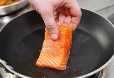Cuoco unico che mette raccordo di color salmone sulla vaschetta calda Fotografia Stock