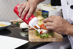Cuoco unico che mette salsa al pomodoro all'hamburger fotografia stock libera da diritti