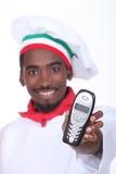 Cuoco unico che passa un telefono. immagine stock