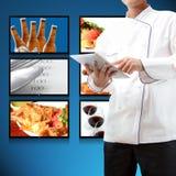 Cuoco unico che per mezzo della compressa digitale Fotografia Stock
