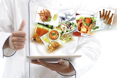 Cuoco unico che per mezzo della compressa digitale Immagini Stock