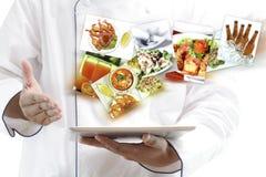 Cuoco unico che per mezzo della compressa digitale Immagine Stock