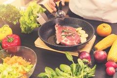 Cuoco unico che prepara bistecca con la patata in una pentola Immagine Stock