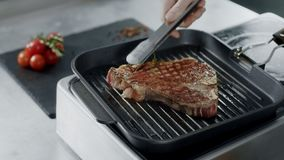 Cuoco unico che prepara carne alla piastra Mani del cuoco unico del primo piano che girano bistecca con le tenaglie stock footage
