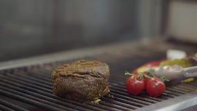 Cuoco unico che prepara carne saporita sulla griglia, girante la con il primo piano delle tenaglie Carboni rossi sul fondo Prepar video d archivio