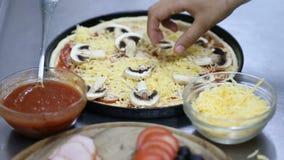 Cuoco unico che prepara pizza metta lo strato dei funghi stock footage