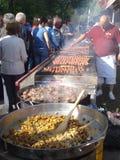 Cuoco unico che preparano i polpettoni arrostiti e la gente che aspetta nella linea per comprare, a Bucarest, la Romania, il 1° m Immagini Stock