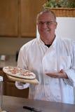 Cuoco unico che presenta pizza congelata Fotografia Stock Libera da Diritti