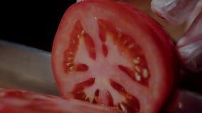 Cuoco unico che produce hamburger Il primo piano equipaggia le mani che tagliano il pomodoro per l'hamburger video d archivio