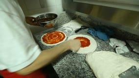 Cuoco unico che spalma masterfully la crosta della pizza di salsa tradizionale specialmente pronta stock footage