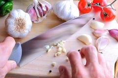 Cuoco unico che taglia aglio a pezzi su una tavola di taglio Immagine Stock