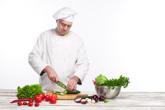Cuoco unico che taglia un cetriolo verde nella sua cucina Immagini Stock