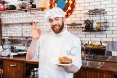 Cuoco unico che tiene bistecca di color salmone sul piatto e che mostra gesto giusto Immagini Stock Libere da Diritti