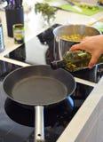 Cuoco unico che va versare olio d'oliva nella pentola Fotografie Stock