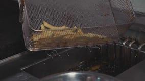 Cuoco unico che versa le patate fritte pronte in ciotola d'acciaio alla cucina commerciale archivi video