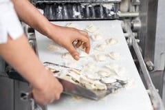Cuoco unico Collecting Ravioli Pasta dalla macchina a Immagini Stock