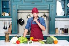 Cuoco unico con il dito di gesto di silenzio alla tavola con le verdure Piatto segreto del cuoco dell'uomo in cucina Ingredienti  Fotografia Stock