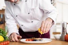 Cuoco unico con il piatto di rifinitura di diligenza sul piatto, pesce con le verdure immagine stock