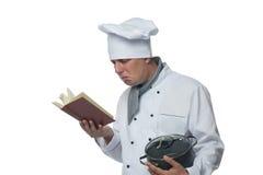 Cuoco unico con il vaso nel suo mano che un libro di ricetta guarda Fotografie Stock Libere da Diritti