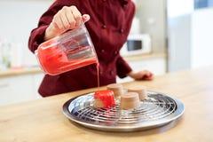 Cuoco unico con la glassa di versamento della brocca da agglutinare al negozio di pasticceria Fotografia Stock