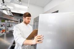 Cuoco unico con la lavagna per appunti che fa inventario alla cucina immagini stock