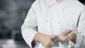 Cuoco unico con le tenaglie del metallo alla cucina professionale Mani maschii del primo piano con le tenaglie archivi video