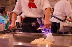 Cuoco unico del ristorante di Hibachi che prepara pasto e gli ospiti divertenti Fotografie Stock Libere da Diritti