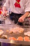 Cuoco unico del ristorante di Hibachi che prepara pasto e gli ospiti divertenti Fotografia Stock