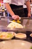 Cuoco unico del ristorante di Hibachi che prepara pasto e gli ospiti divertenti Immagine Stock