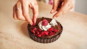 Cuoco unico della donna che prepara il dolce di cioccolato con crema e raspb montati Fotografia Stock