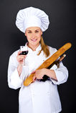 Cuoco unico della donna con pane francese ed il vetro di vino sopra fondo scuro Fotografia Stock